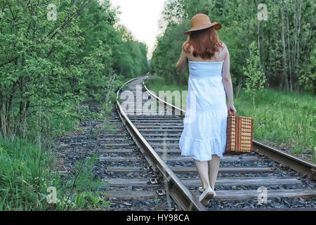 girl in a white sundress and wicker suitcase walking on rails - Stock Photo