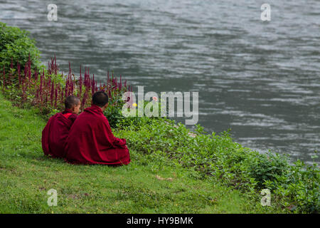 Two young novice Buddhist monks sit in the grass on the bank of the Mo Chhu River at the Punakha Dzong in Punakha, - Stock Photo