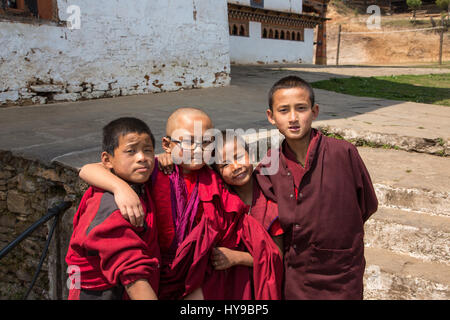 Four young novice monks in the Talo Buddhist Monastery pose for their picture.  Talo, Bhutan. - Stock Photo