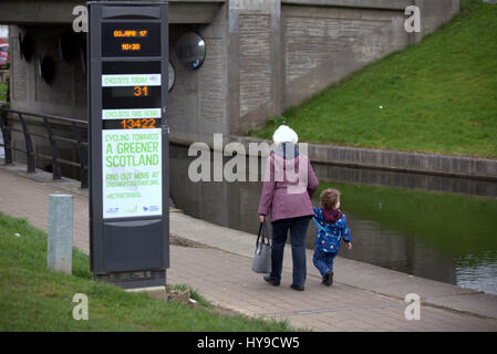 greener scotland #activetravel passing pedestrians  granny and grandchild on the forth clyde canal cycle path - Stock Photo