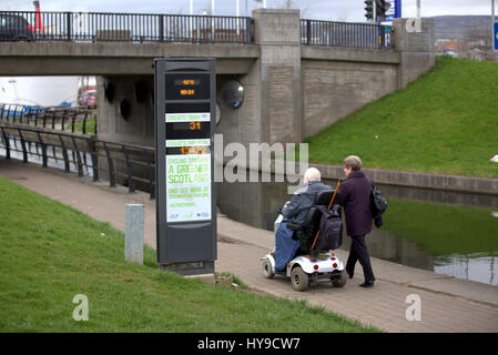 greener scotland #activetravel passing pedestrians carer and mobility scooter  on the forth clyde canal cycle path - Stock Photo