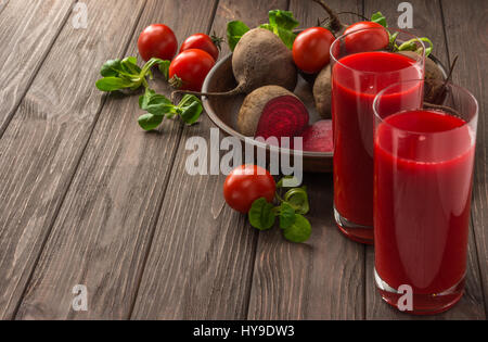 Healthy eating, dieting and vegetarian concept - glass juges of beet-tomato juice with vegetables on dark wooden - Stock Photo