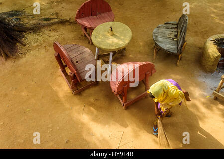 Young lady sweeping in the early morning light with copy space - Stock Photo