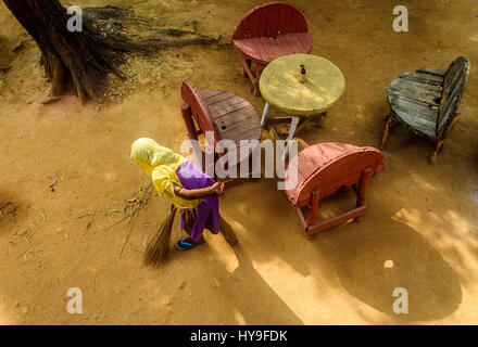 Young lady sweeping the courtyard with broom in the early morning light with copy space - Stock Photo