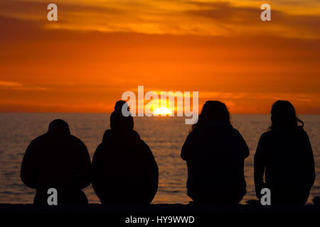 Aberystwyth Wales, UK. 2nd Apr, 2017. UK Weather: Four young people sitting in silhouette watching the setting sun - Stock Photo