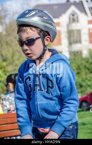 A boy in the park wearing a bicycle helmet and sunglasses. - Stock Photo