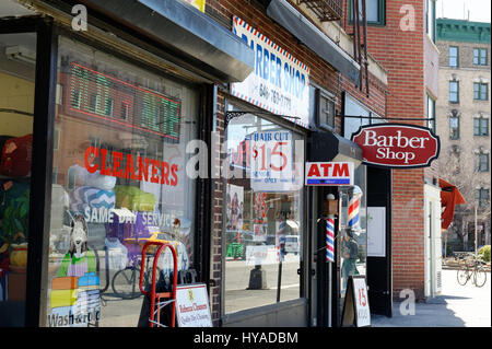 A dry cleaners and an old-fashioned barber shop are among the stores on Seventh Avenue in Greenwich Village, Manhattan. - Stock Photo