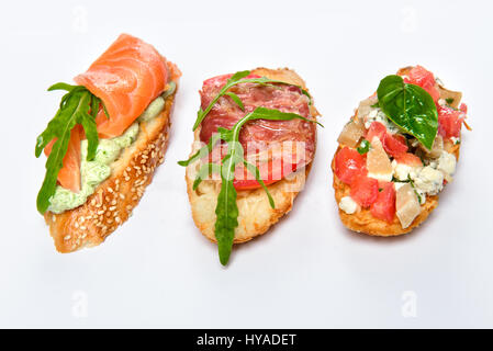 Three different bruschettes with greens, cheese, meat and fish - Stock Photo