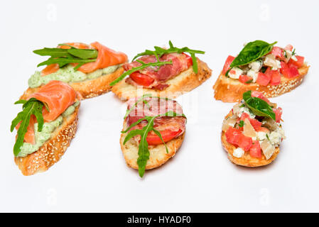Six bruschettes with greens, cheese, meat and fish - Stock Photo