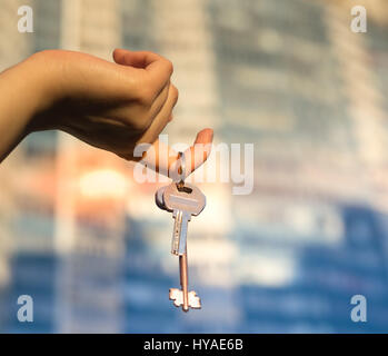 Hand holding key with modern building on background. Buying new home or flat concept. - Stock Photo
