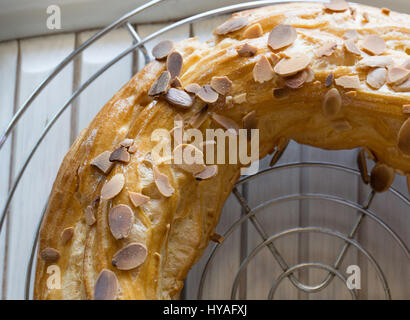 Freshly baked large profiterole cake filled in with covered with roasted almonds and chocolate flakes cooling down - Stock Photo