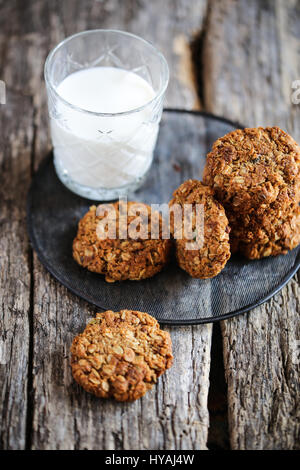 traditional anzac oat cookies and glass of milk on a wooden background - Stock Photo