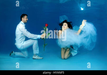 ALL ROUND EXCLUSIVE. ODESSA, UKRAINE: Bride and groom pose for underwater snap showing their courtship. NEWLYWEDS - Stock Photo