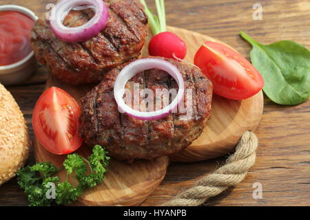 beef burger with onion and sauce on cutting board - Stock Photo