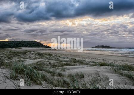 Atmospheric sky at sunrise over Conjola Beach, Shoalhaven, South Coast, New South Wales, NSW, Australia - Stock Photo