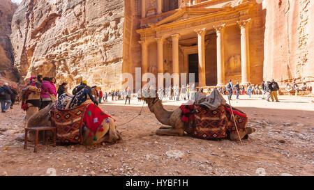 PETRA, JORDAN - FEBRUARY 21, 2012: camels and people near al-Khazneh temple (The Treasury) in ancient Petra. Rock - Stock Photo