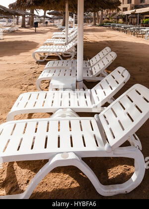 Travel to Middle East country Kingdom of Jordan - empty loungers Coral beach of Red Sea in Aqaba city in winter - Stock Photo