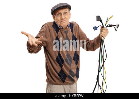 Baffled senior holding different types of electronic cables and looking at the camera isolated on white background - Stock Photo