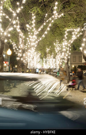 White carnival festival lights at Avenida Arriaga, Funchal, Madeira reflect on a passing car - Stock Photo