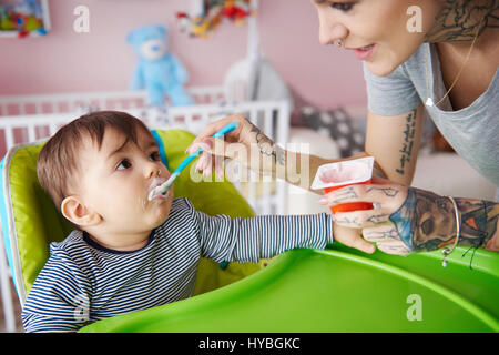 Baby boy eating in his high chair - Stock Photo