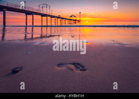 Human footprints in wet sand at sunset, South Australia - Stock Photo