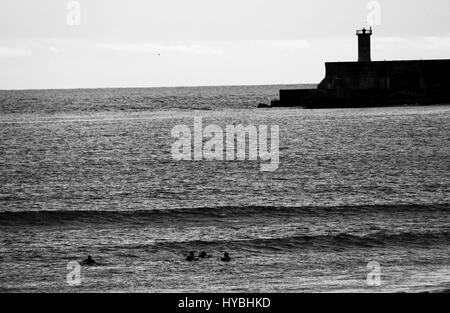 Some surfers at Matosinhos beach with the lighthouse as a scenario. - Stock Photo