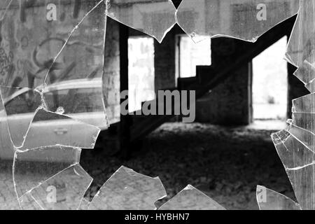 A black and white shot of a broken window of an abandoned house in the centre of Matosinhos, Porto, Portugal. - Stock Photo