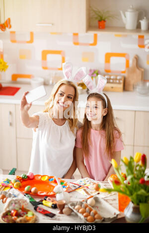 Mother with daughter take selfie in kitchen while preparing Easter  eggs - Stock Photo