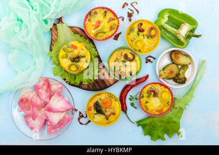 Omelette with colored pasta, mushrooms, vegetables and herbs, cooked in the form of mafins. The top view. Breakfast. - Stock Photo