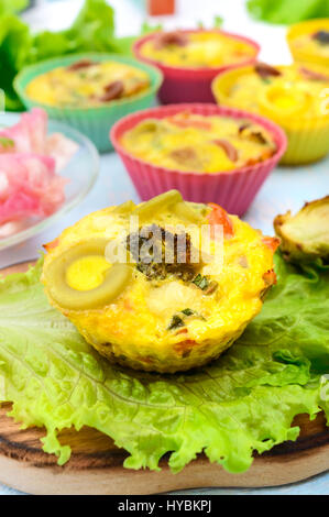 Omelette with colored pasta, mushrooms, vegetables and herbs, cooked in the form of mafins.  Breakfast. - Stock Photo