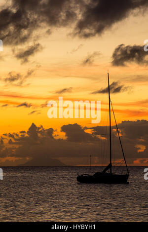 Sailboat silhouetted against sunset in Dickenson Bay, Antigua. - Stock Photo