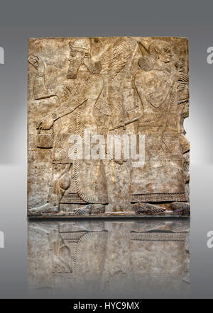 Assyrian relief sculpture panel  of a female protective spirits  from Nimrud, Iraq.  865-860 B.C North West Palace. - Stock Photo