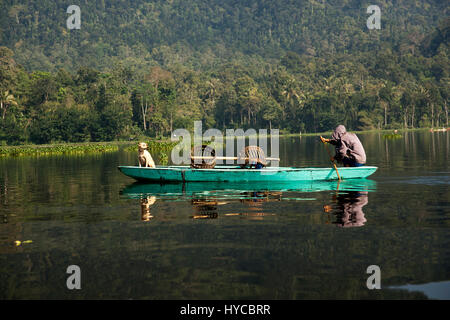 Yellow golden dog sitting on a boat going down the river looking at master and fisherman who is rowing the boat - Stock Photo