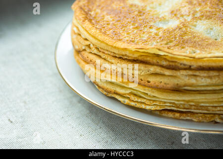 Stacked golden crepes on white plate on linen cloth background, closeup, breakfast, cozy morning atmosphere - Stock Photo