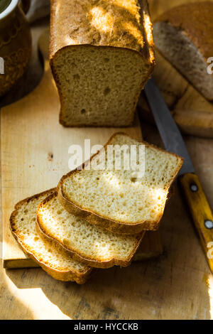 Loaf of sourdough bread cut into slices on wood cutting board, knife, kitchen table, sunlight flecks, cozy morning - Stock Photo