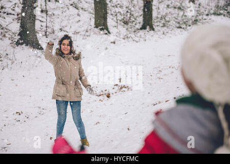 Girl throwing snowball in snowy forest - Stock Photo