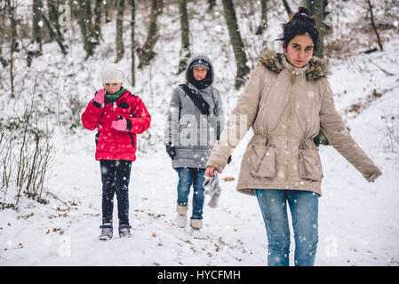 Mother with daughters hiking in white winter forest - Stock Photo