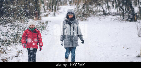 Mother with daughter hiking in white winter forest - Stock Photo