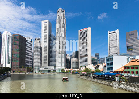 Singapore, July 07, 2013: Touristic boat floating down the Singapore river near the Boat Quay on July 07, 2013 in - Stock Photo