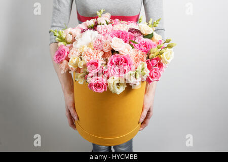 Luxury bouquets of flowers in the hat box. roses in the hands of women.