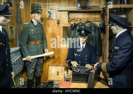 German WWII officer using 3-rotor Wehrmacht Enigma machine at Raversyde Atlantikwall / Atlantic Wall museum at Raversijde, - Stock Photo