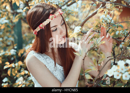 Young woman in a flowered orchard. Spring seasonal - Stock Photo
