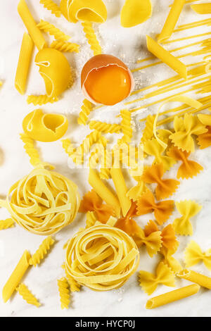Various types of pasta on marble with egg - Stock Photo