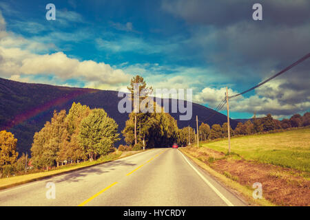 Mountain road at sunset with cloudy sky. Autumn nature Norway after rain. Rainbow over road - Stock Photo