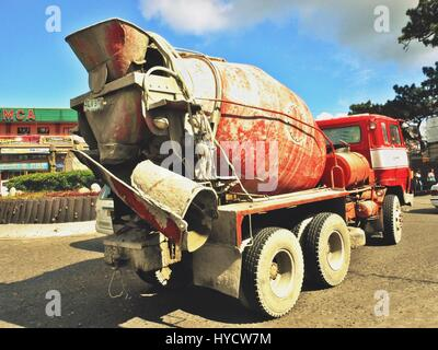 Red cement mixer truck  traversing Session Road in Baguio City, Philippines - Stock Photo