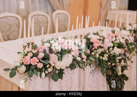 Wedding table decoration in the tenderly light pink style with roses, carnations and candles - Stock Photo