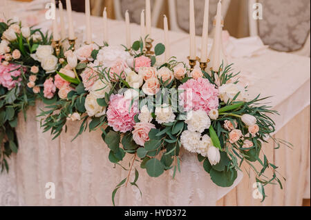 Wedding table decoration with roses, carnations and candles in the tenderly light pink style - Stock Photo