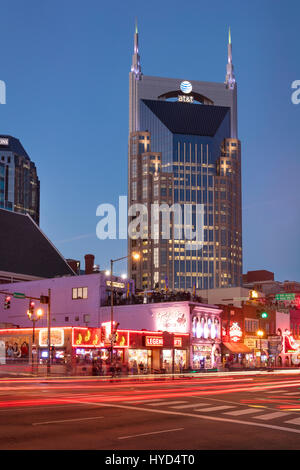 AT&T Building towers over music clubs along lower Broadway in downtown Nashville, Tennessee, USA - Stock Photo