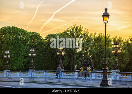Paris, France - May 18, 2015 : lone passerby on Alexander III bridge  over the Seine in Paris between des Invalides - Stock Photo