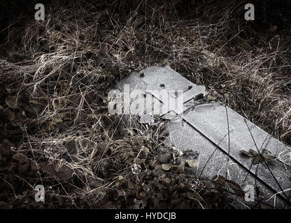 Brompton, London - Unmarked gravestone with medieval cross engraving in dark, moody setting - Stock Photo
